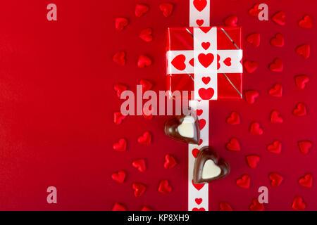 Cadeau et chocolat et coeur rouge sur rouge Banque D'Images
