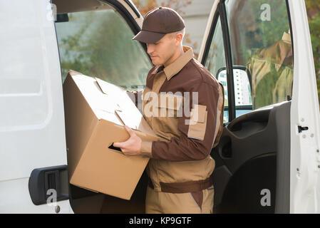 L'homme dépose de boîte en carton de livraison d'un camion Banque D'Images