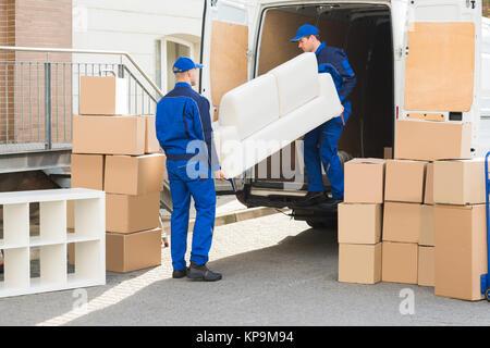 Le déchargement du camion canapé déménageurs Banque D'Images