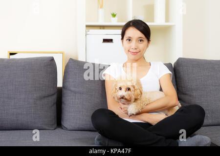 Femme et de l'Asie à la maison chien caniche Banque D'Images