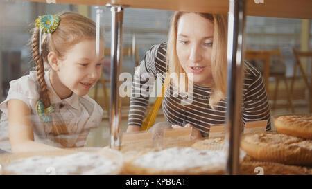 Fille avec une queue de cochon et sa mère regarder les graphiques dans la fenêtre Choisir Banque D'Images