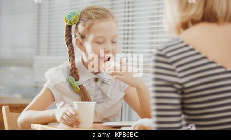 Fille avec des tresses mange les gâteaux avec sa maman dans le café Banque D'Images
