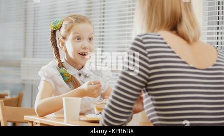 Girl with pigtails avec sa maman dans le café - teen se sent surpris Banque D'Images