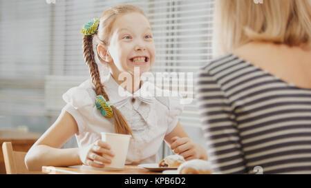 Mère et fille sont assis dans un café, manger émotionnellement parlant sweetsand Banque D'Images