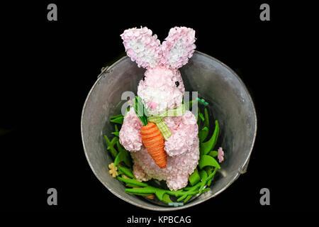 Lapin de Pâques rose fabriqué à partir de pétales de fleurs avec cour carotte dans un seau avec des fleurs isolé Banque D'Images