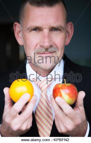 Man holding orange et apple dans ses mains Banque D'Images