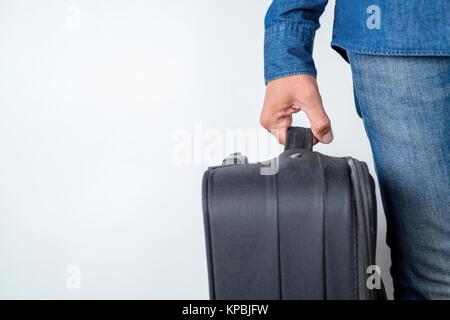 Libre d'un young caucasian man wearing jeans et chemise en jean, portant une valise par la poignée contre un fond Banque D'Images