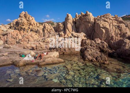 Femme prend un bain de soleil à l'idyllique côte rocheuse de Costa Paradiso, rochers de porphyre, Sardaigne, Italie, Banque D'Images