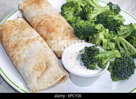 Rempli deux tortillas avec un côté du brocoli frais et un contenant de sauce crémeuse pour tremper Banque D'Images