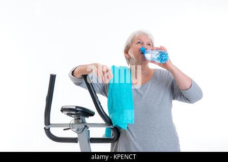 Femme aux cheveux gris avec de l'eau principal de la bouteille avec la machine de remise en forme Banque D'Images