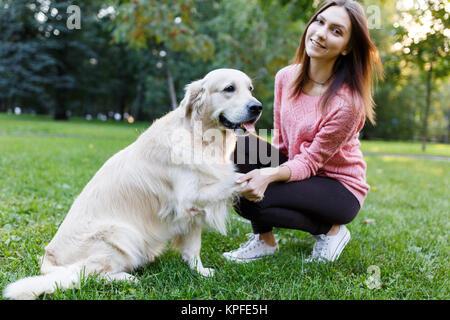 Image de la femme avec chien patte donnant sur pelouse au parc d'été