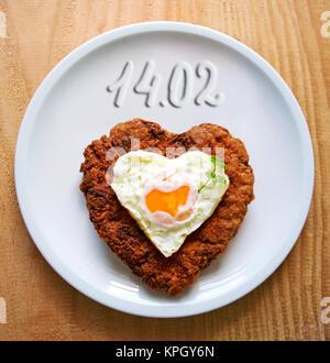 Steak haché en forme de cœur avec l'œuf frit sur plaque blanche.le jour de la Saint-Valentin. Banque D'Images