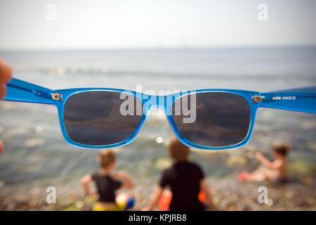 À la recherche à travers une paire de lunettes bleu à trois jeunes garçons jouant sur une plage Banque D'Images