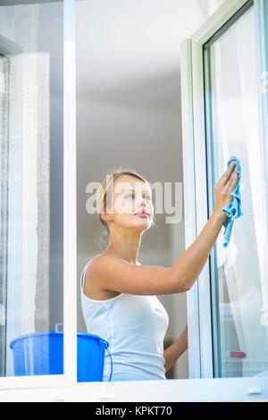 Jolie jeune femme travail maison - laver les vitres Banque D'Images