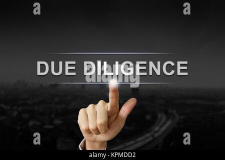 La main d'affaires due diligence en poussant sur le bouton Arrière-plan flou noir Banque D'Images