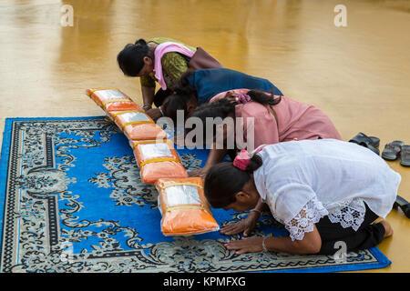 Bangkok, Thaïlande. Wat Saket (Phu Khao Thong), le Mont d'or. Les fidèles prient avant de quitter les dons de tissu Banque D'Images