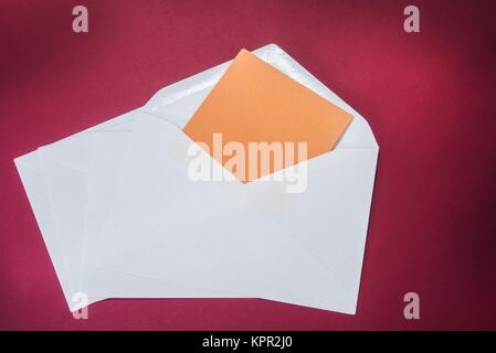 L'un ouvert enveloppe blanche sur le fond rouge Banque D'Images