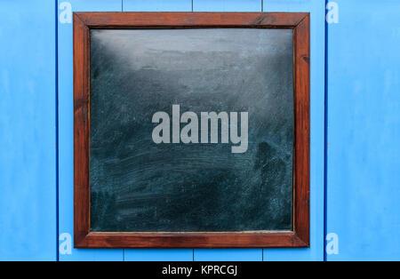 Cadre en bois blanc sur le mur. Tableau noir à l'intérieur et fond bleu clair, de l'espace pour le texte.