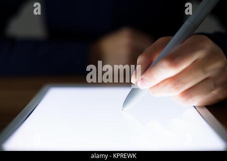 Femme d'écrire quelque chose sur la tablette numérique Banque D'Images