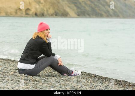 Une fille est assise sur la plage un jour nuageux par temps froid et à la recherche dans la distance avec soin