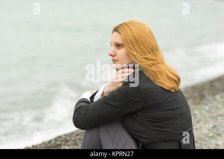 Une fille est assise sur une plage de galets de la mer sur un jour nuageux par temps froid, couvrant le cou foulard