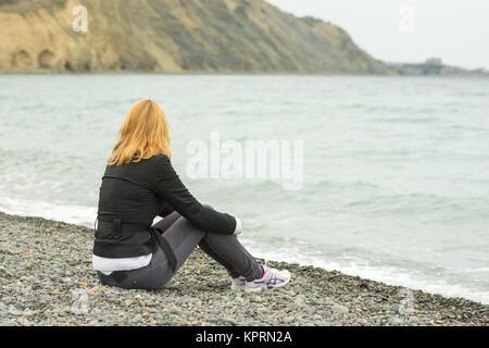 Une fille est assise sur une plage de galets à la mer par temps froid et regarder les vagues