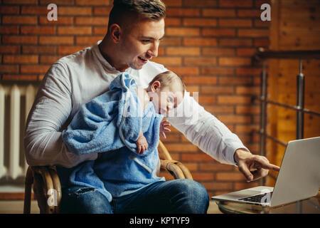 L'homme travaillant au bureau à la maison avec un ordinateur portable, holding cute, écran de babys Banque D'Images