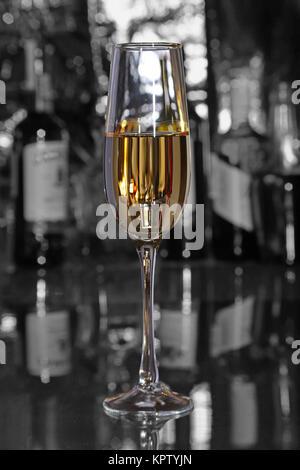 Verre de vin, cognac, brandy ou whiscy sur miroir table. bouteilles dans un bar sur l'arrière-plan Banque D'Images