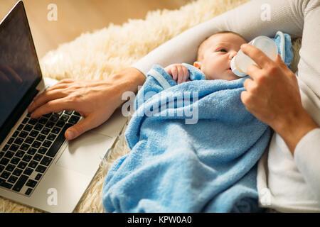 L'alimentation de l'homme petit bébé en position couchée sur le lit et le working on laptop Banque D'Images