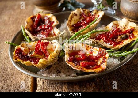 Close Up Portrait of Plate of Kilpatrick huîtres préparées avec du bacon et du fromage et servi sur une table en Banque D'Images