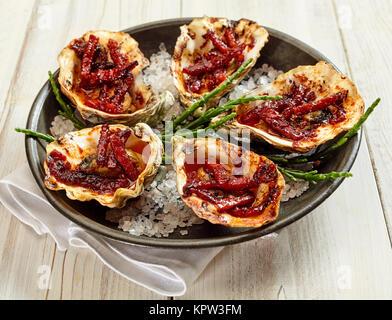 Angle de vue de la vie toujours élevé d'assiette d'Huîtres Kilpatrick préparé avec du bacon et du fromage et servi Banque D'Images