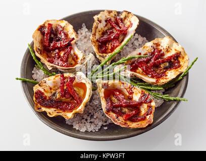 Close Up Still Life sur une assiette d'Huîtres Kilpatrick préparé avec du bacon et du fromage et servi avec du sel Banque D'Images