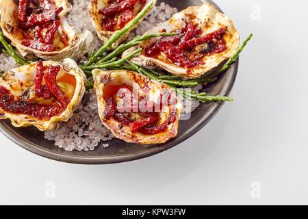 Close Up Still Life sur une assiette d'Huîtres Kilpatrick préparé avec du bacon et du fromage et servi sur fond Banque D'Images
