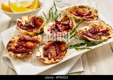 Close Up Still Life Voir des huîtres, assiette de Kilpatrick préparé avec du bacon et du fromage et servi sur table Banque D'Images