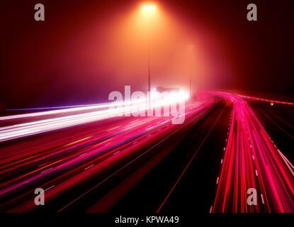 Résumé artistique feu sentiers dans le cadre d'une route très fréquentée à l'heure de pointe sur une nuit brumeuse, Banque D'Images
