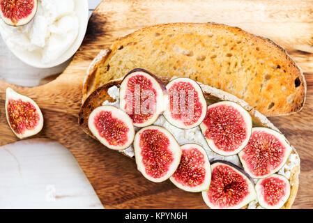 Collation santé de pain au levain toasts, figues et ricotta sur planche de bois Banque D'Images