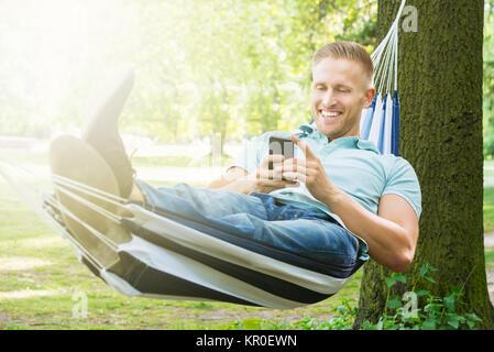 Homme étendu dans un hamac à l'aide de Mobile Phone