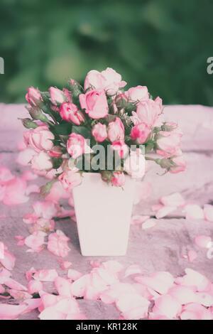 Roses dans vase blanc sur une table en bois Banque D'Images