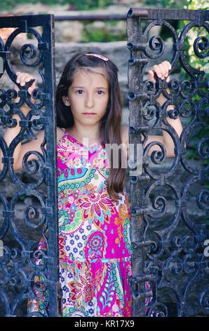 Belle jeune fille regardant derrière la porte en fer forgé dans le Jardin botanique de Balchik, Bulgarie. Banque D'Images