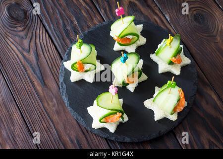 Canape apéritif avec du pain blanc, de concombre, de ricotta et de langoustines sur une table en bois. Banque D'Images
