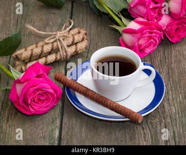 Still Life café, biscuits en forme de bâtonnets et une rose de chaque côté Banque D'Images
