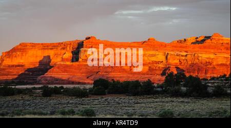 Coucher du soleil jette une lueur rouge sur les roches de la zone d'aiguilles dans Canyonlands National Park, en Banque D'Images