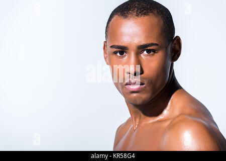 Close-up portrait of young shirtless african american man looking at camera isolé sur gray Banque D'Images