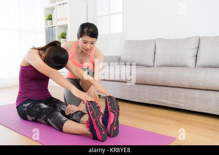 Belle jeune étudiante qui s'étend du corps et utiliser les mains de toucher les jambes avec sa formation des enseignants Banque D'Images