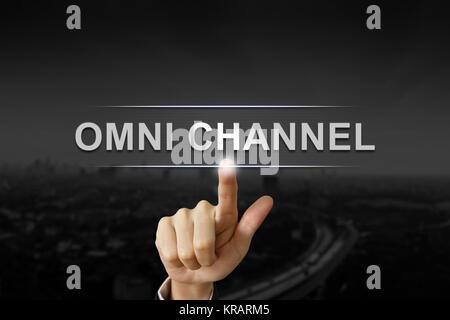 La main d'affaires en poussant le bouton Canal omni noir sur fond flou Banque D'Images