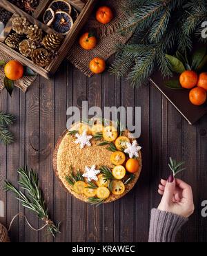 Femme Noël décore gâteau au miel de romarin et oranges sur fond de bois brun.
