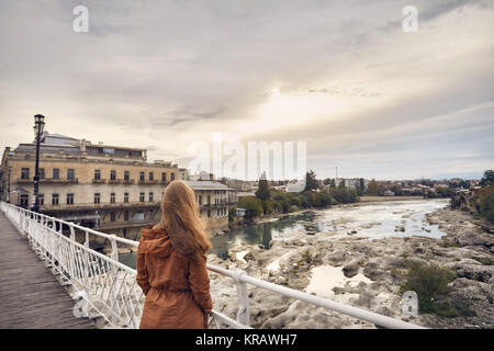 Femme seule avec de longs cheveux sur le pont à la recherche au lever du soleil à Kutaisi, Géorgie Banque D'Images