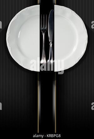 Restaurant avec menu vide et plaque blanche avec fourchette et couteau sur fond ondulé noir et gris avec des rayures Banque D'Images