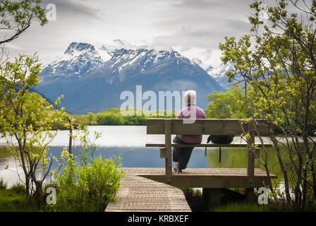 Une dame assis à admirer la vue traverser la Glenorchy lagon de l'île du sud de Nouvelle-Zélande. Novembre 2007 Banque D'Images
