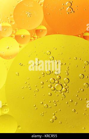 Des gouttelettes d'huile d'orange et jaune sur l'eau Banque D'Images